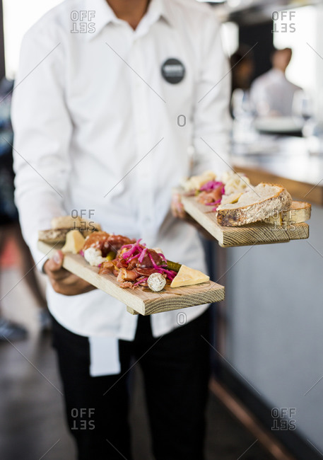 Server carrying appetizers at a restaurant