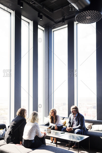 Four people having conversation around a coffee table
