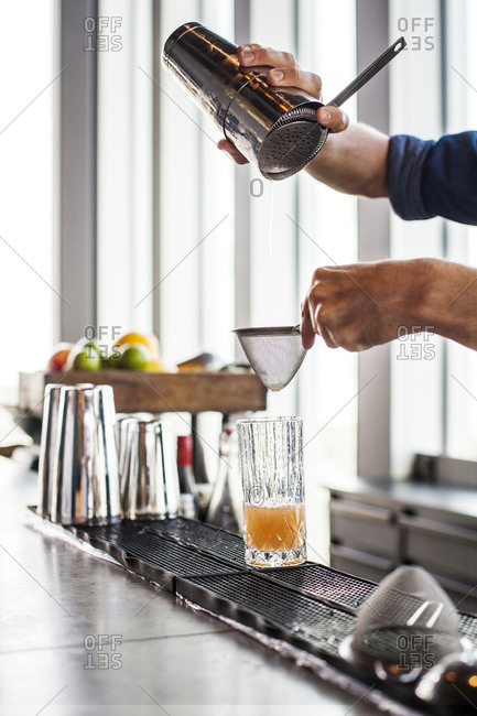 Bartender pouring and straining cocktail