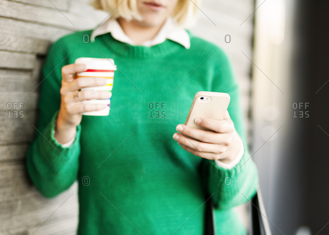 Woman leaning on building with coffee in hand and looking at her phone close up