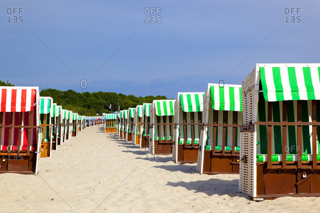 Two rows of hooded beach chairs at beach