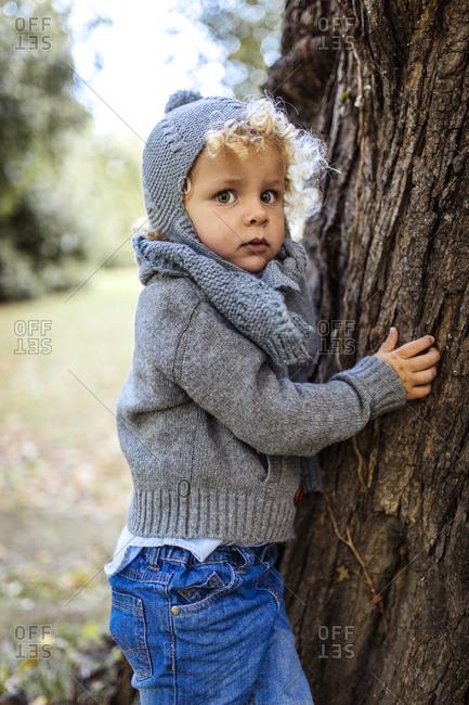 Portrait of little boy wearing autumn fashion besides a tree trunk