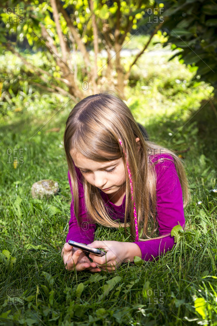 Little girl lying on a meadow in the garden looking at smartphone