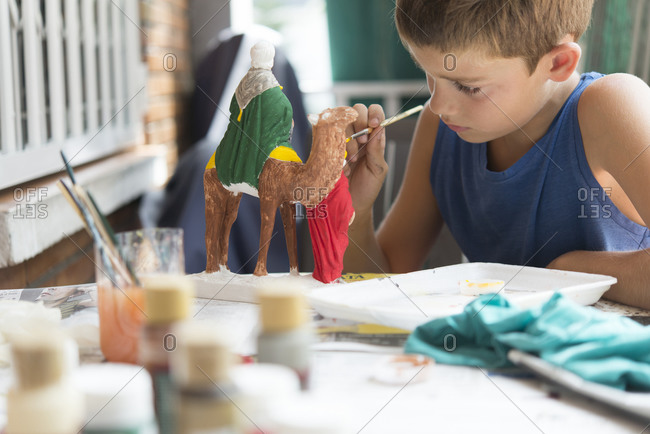 Boy painting nativity figurines