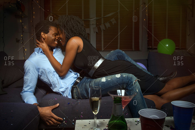 Couple kissing on a couch during party