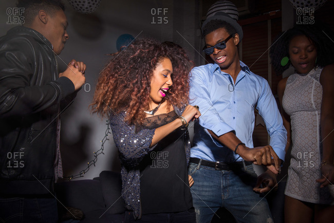 Stylish friends dancing together at house party