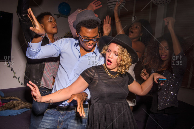 Stylish friends dancing at house party