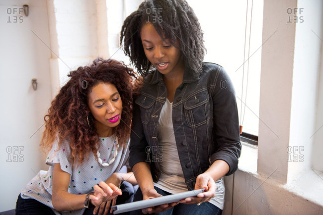 African American women in loft with tablet
