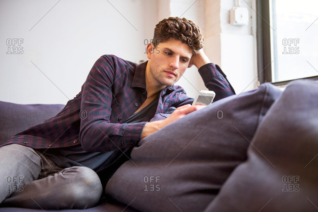 Caucasian man reading phone on couch in loft