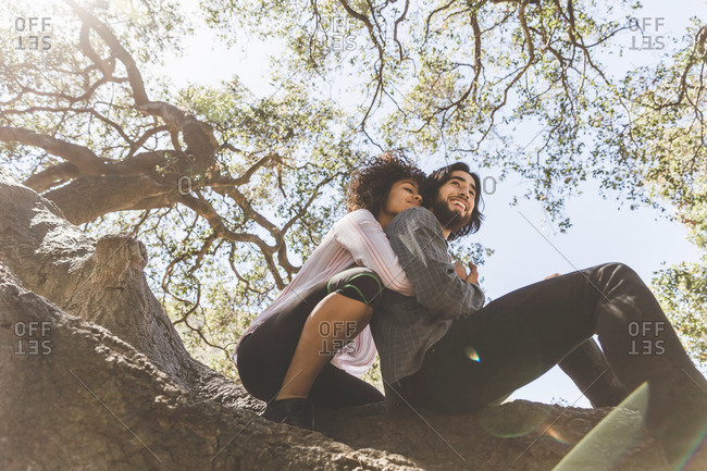 Young couple with arms around each other in a tree