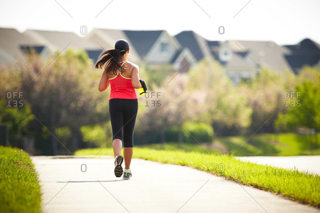 Rear view of woman jogging in suburbs