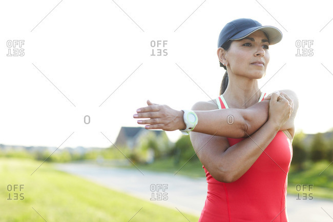 Close up of female jogger stretching her arms