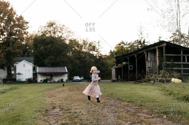 Little girl running across a rural backyard