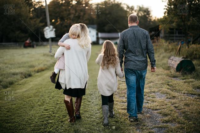 Family walking across a field towards home