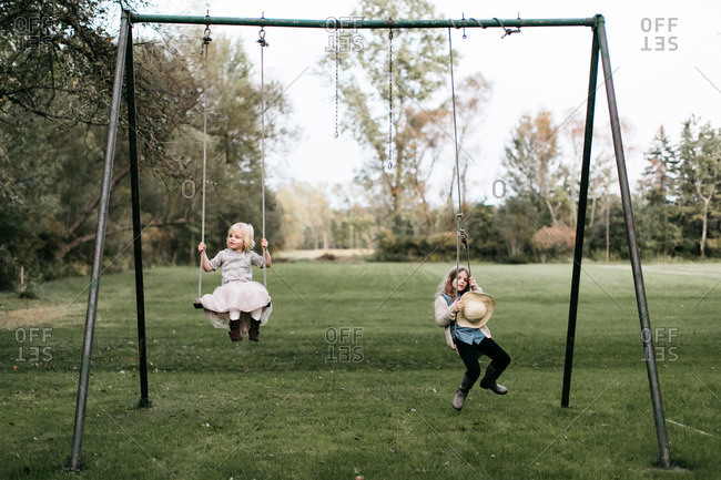 Sisters playing on a swingset