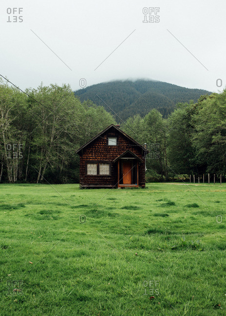 Rustic wood cabin in a field below mountain