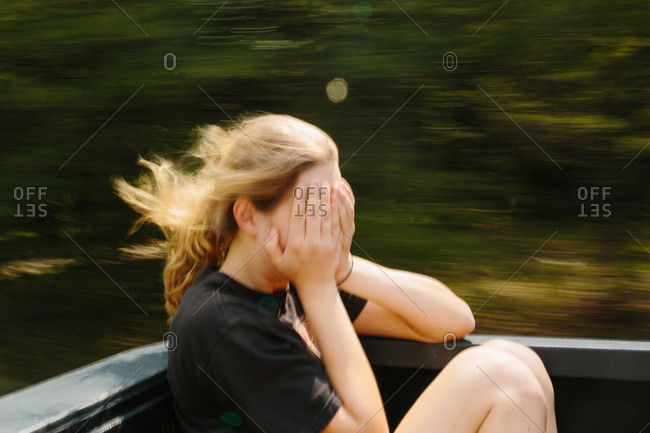 Young woman riding in back of pickup truck with hands covering her face
