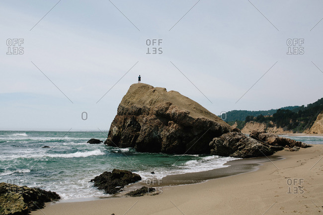 Person standing atop a rock on ocean beach