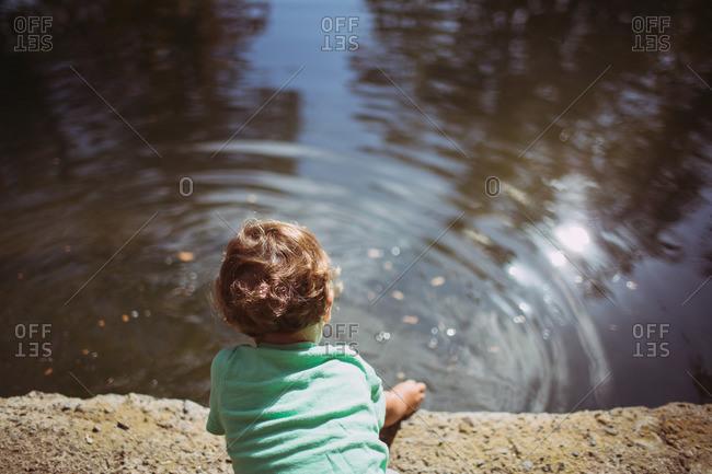 Boy making ripples in lake water