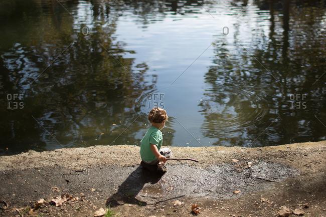 Boy making ripples in lake surface
