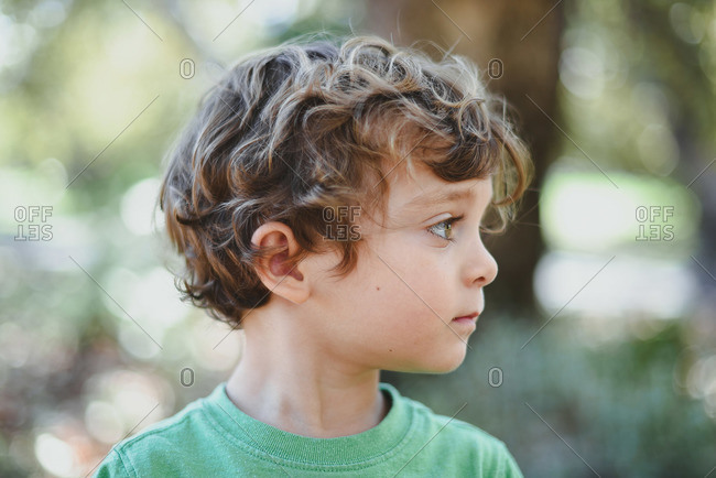 Profile of wavy haired boy in rural setting