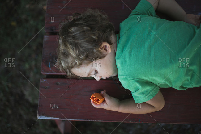Boy sleeping on bench outside holding a toy
