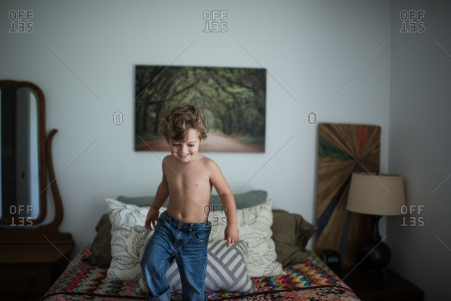 Shirtless boy smiling while standing on bed