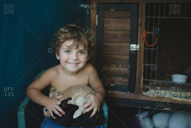 Smiling boy in chair holding a pet bunny