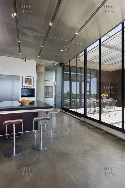 Minneapolis, MN, USA - May 26, 2011: Counter and stools in modern kitchen loft with view to deck