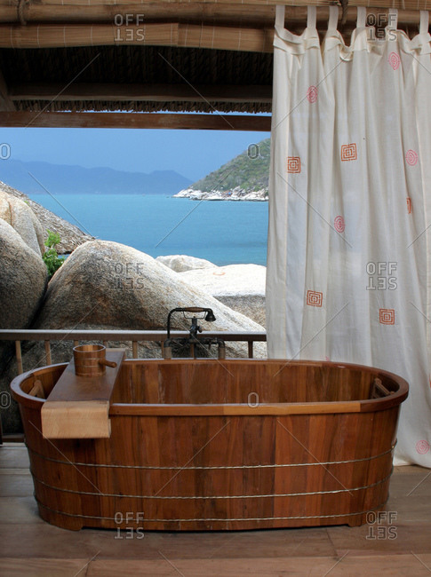 Nha Trang, Vietnam - February 21, 2004: Wooden bathtub with coastal view at Evason Hideaway