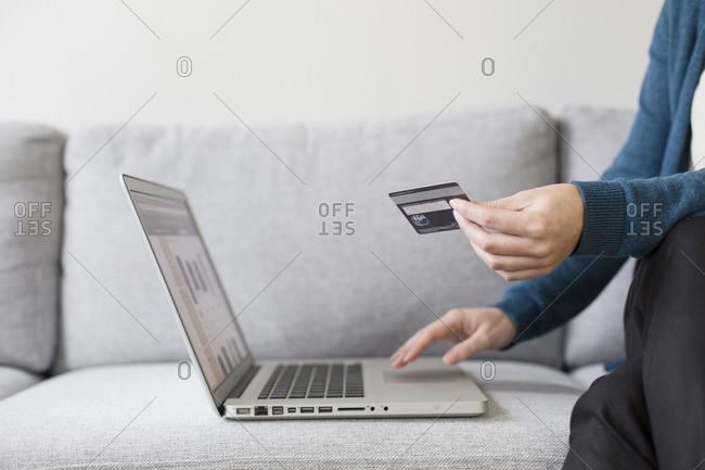 Woman typing credit card information on a laptop