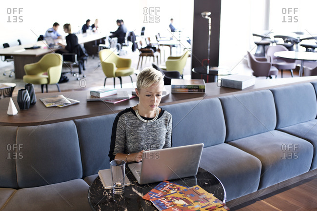 Woman with laptop in employee lounge