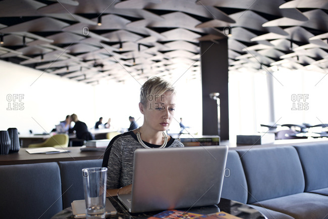Woman with laptop in office lounge