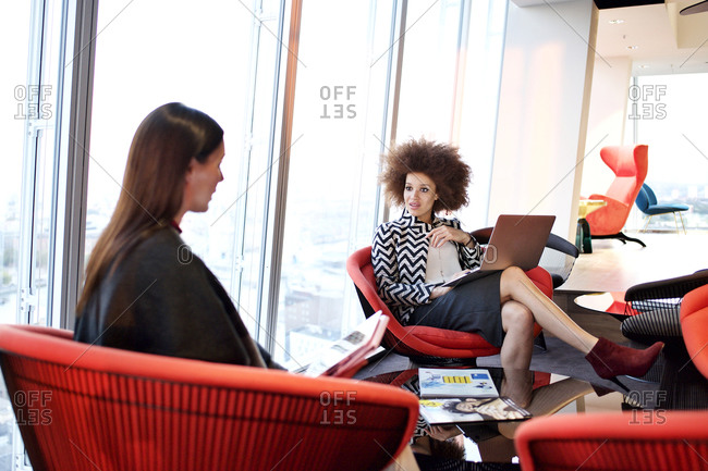 Female office workers sitting in office lounge