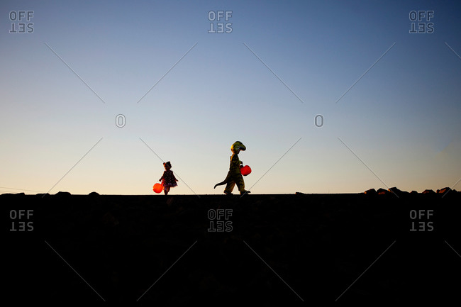 Silhouette of two kids trick or treating