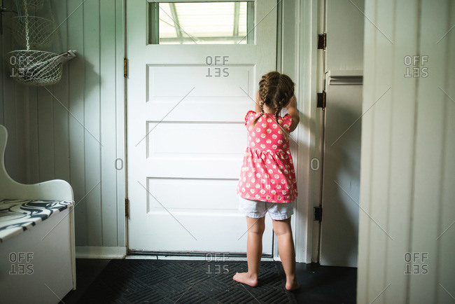 Little girl opening a door Little girl opening a door & door open stock photos - OFFSET