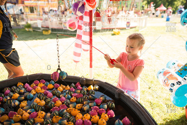 Little girl playing a fishing game at a fair
