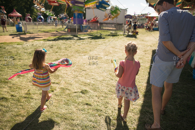 Father and daughters walking through fairgrounds carrying prizes