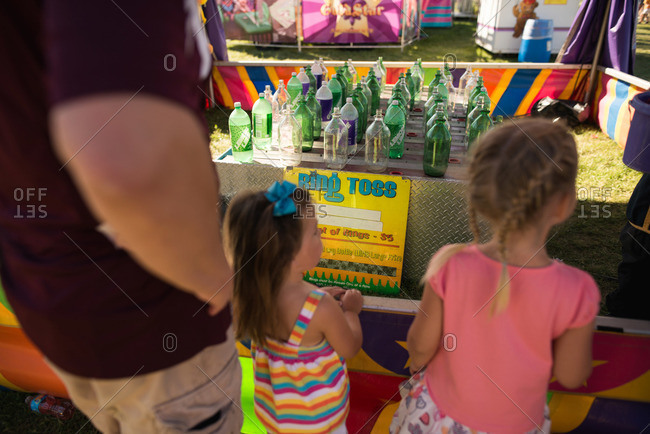 Girls standing at a ring toss game at a fair