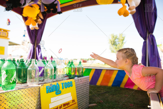 Little girl playing a ring toss game at a fair