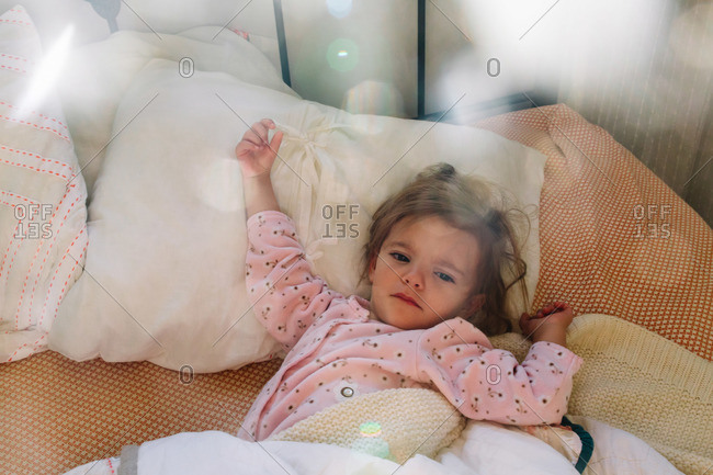 Little girl lying in bed waking up