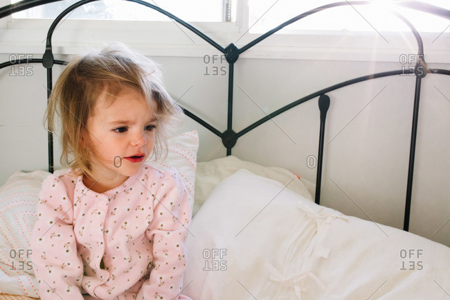 Little girl sitting in bed after waking up