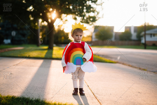 Girl in a rainbow costume standing in a driveway