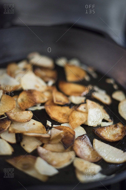 Potato slices cooking in a cast iron pan