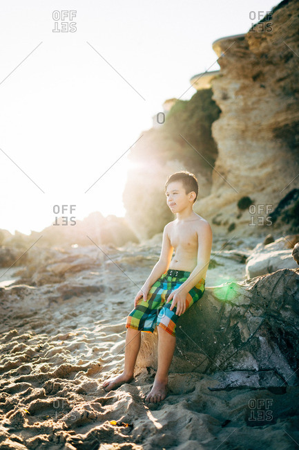 Boy sitting on boulder on beach staring off