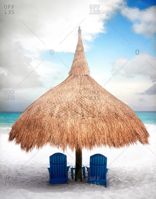 A beach palapa with two blue chairs in Mexico