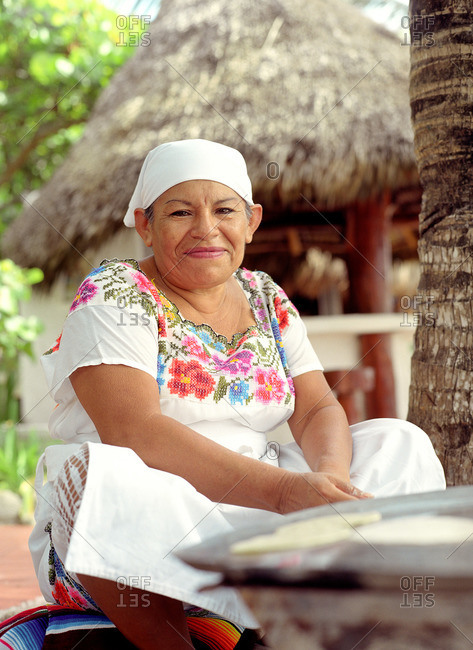 A Mexican woman makes tortillas by the beach at a resort