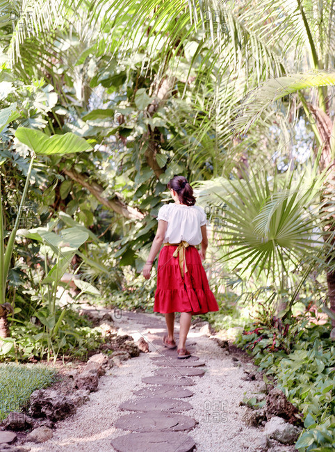 Woman in red skirt walking down garden path at tropical resort
