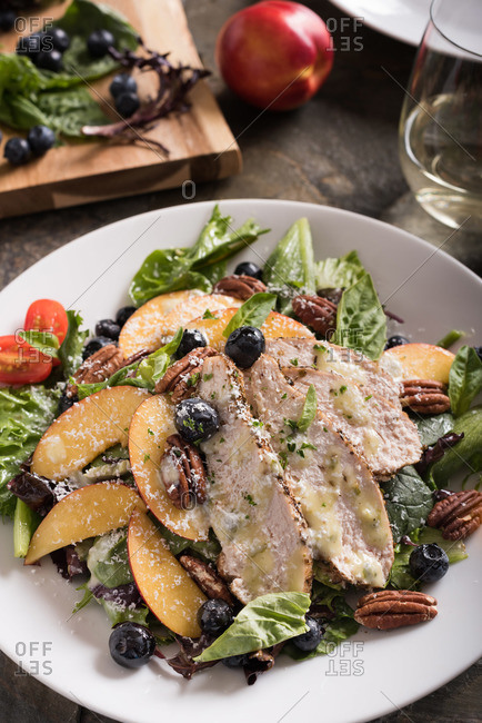 A summer salad of nectarines, blueberries, grilled chicken, pecans, cherry tomatoes, finished with parmesan cheese shavings.