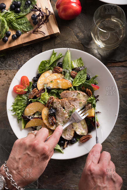 Hands cutting salad with grilled chicken, nectarines, blueberries and cherry tomatoes